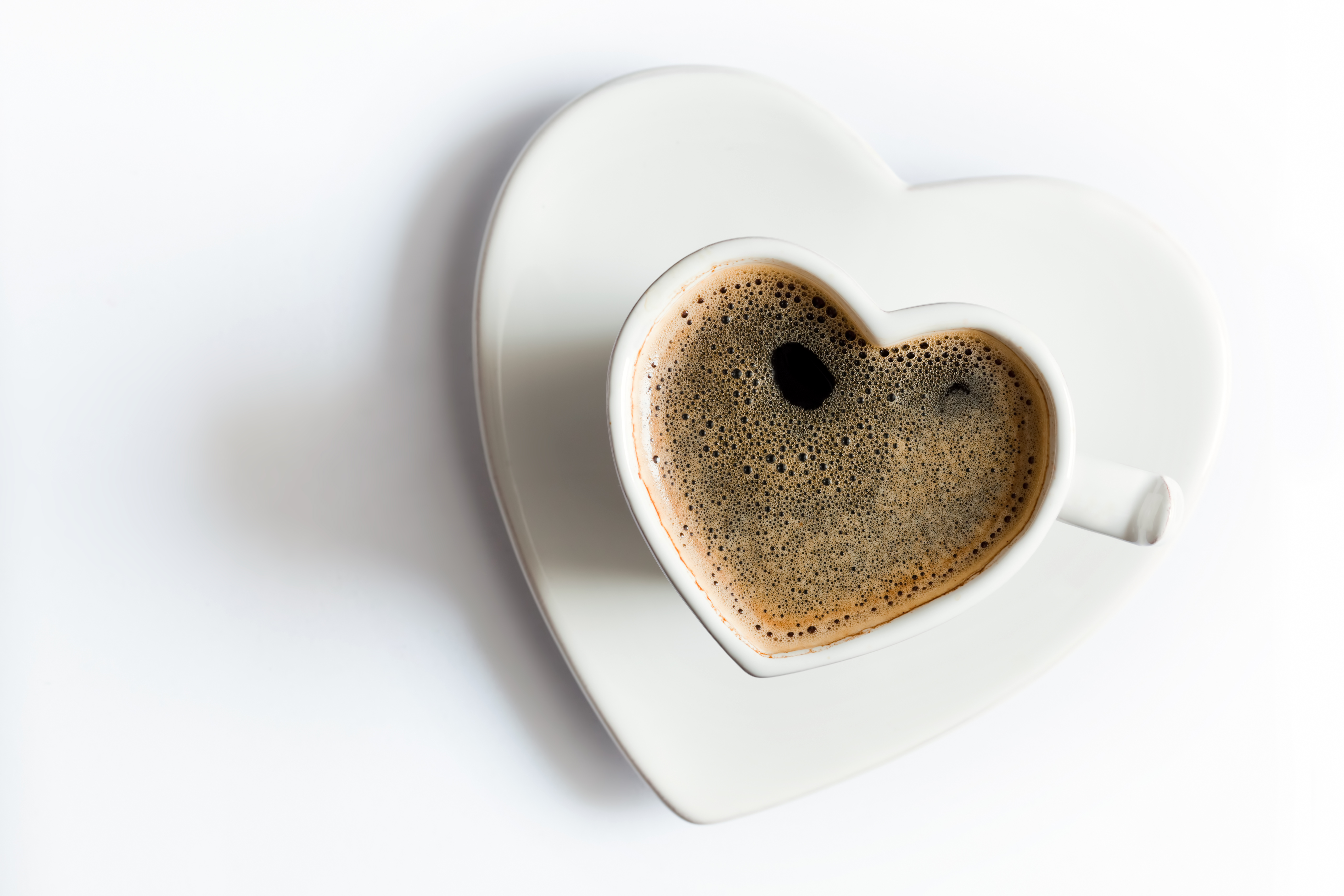 Heart shaped cup of black coffee on white. Love